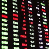 Stock prices reported on a black reporting board